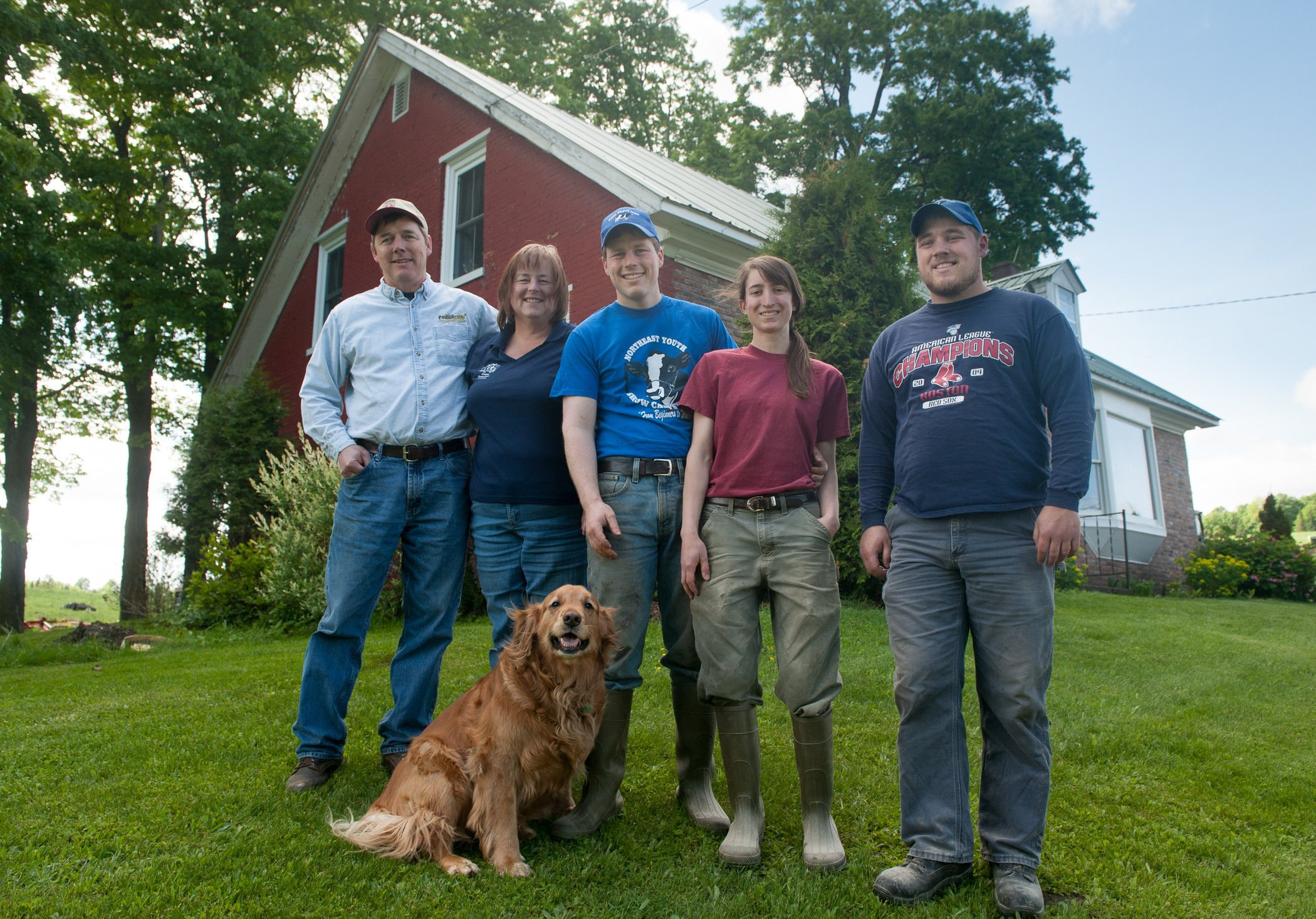 Family of five farmers and a dog standing in front of their red house